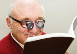 This is a picture of an gentleman reading a book with the help of bioptic glasses. Bioptics are just one of many tools available to assist people in reading.