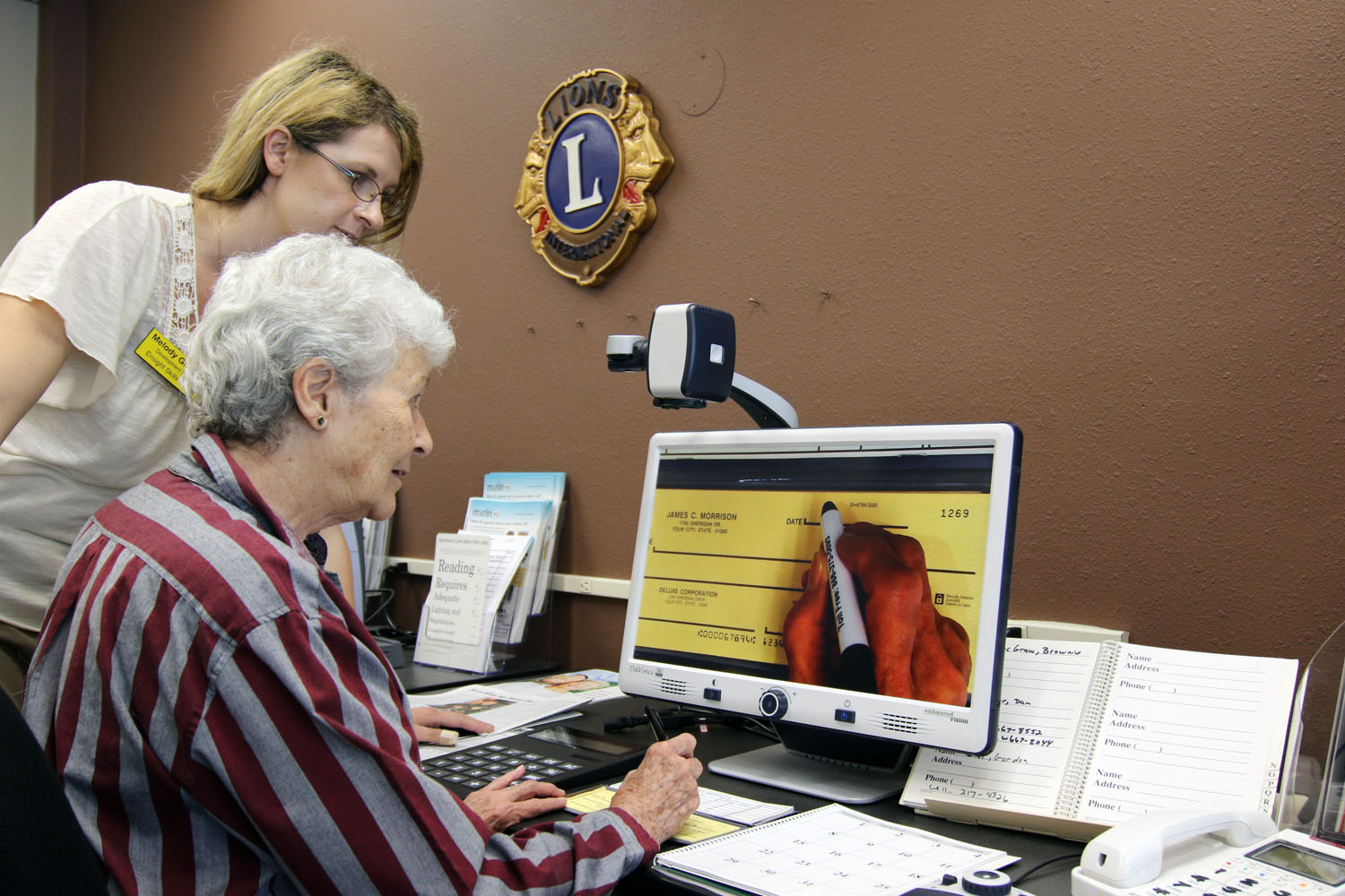 Low vision specialists helping woman use a closed circuit TV