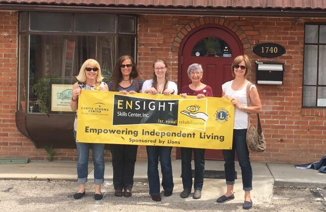People hold Ensight sign saying empowering independent living