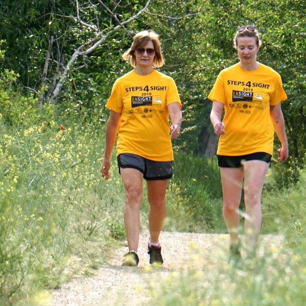 two women walking on trail with Ensight t-shirts