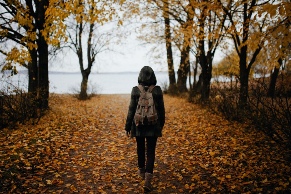 woman walking on leaf-covered path