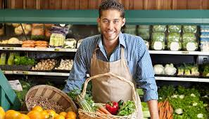 grocery clerk standing behind produce counter